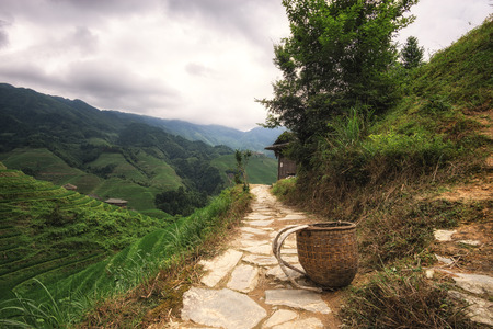 rice terrace: Small basket used by the local farmer laid carefully on the trail leading up to the viewpoint number 2 thousand layers of heaven in Longji rice terrace, China Stock Photo