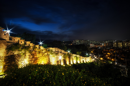 Naksan Fortress Wall taken at night with the seoul city in the background. Naksan is a famous small park in daehangno, seoul, south korea.