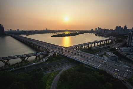 turnabout: mapo bridge view from top of a building, sunset shining on the traffic during rushhour in seoul, south korea Stock Photo