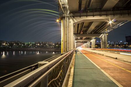 view of han river from banpo bridge taken during banpo rainbow fountain show with the motion of cars passing by