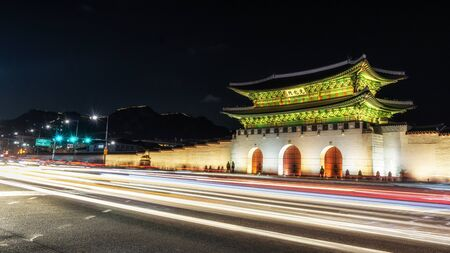 main entrance: Gyeongbok Palace gate taken at night with the fast moving traffic car trails in front of the gate. Gyeongbok Palace is a famous landmark in Seoul, South Korea.
