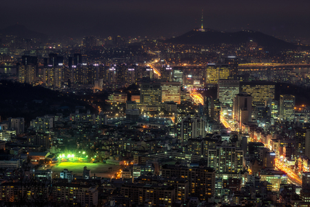 gangnam: Gangnam and busy seocho district at night with the seoul n tower in the distance covered by the smog. traffic and city light illuminating the city.