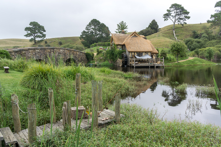 arched: hobbiton mill and double arched bridge with lake reflection in hobbiton movie set, new zealand.