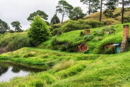 reflecting: hobbit holes in hobbiton movie set reflecting in a small lake. Taken in New Zealand.