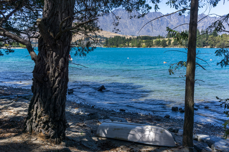 kelvin: queenstown gardens park view with the small boat in the foreground. Lake wakatipu and mountains in background. Stock Photo