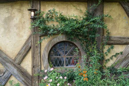 travel features: green dragon tavern wall with a small round window. Taken in hobbiton movie set in new zealand.