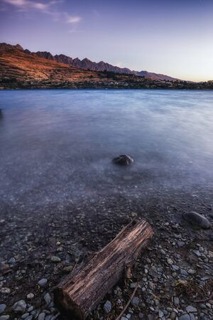 kelvin: a small rock in lake wakatipu with kelvin heights in the background. Taken near queenstown, New Zealand.