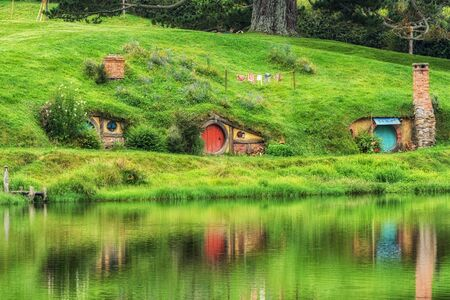 hobbit holes in hobbiton movie set reflecting in a small lake. Taken in New Zealand.
