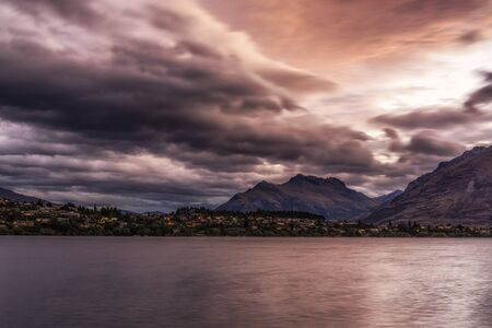 kelvin: storm clouds over lake wakatipu with kelvin heights in the distance. Sunlight covered in stormy clouds. TAken during summer.