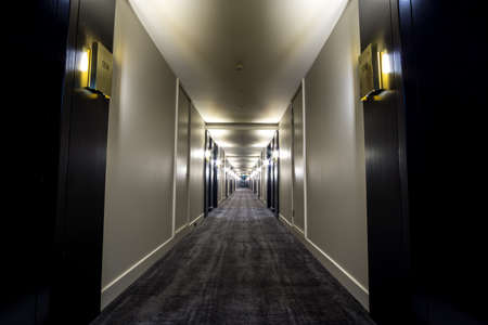 hotel hallway: hotel hallway with endless doors and rooms stretching all the way towards the end.