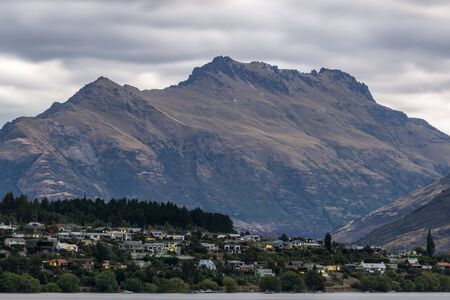 kelvin: sunset over lake wakatipu with kelvin heights in the distance. Sunlight covered in stormy clouds. TAken during summer.