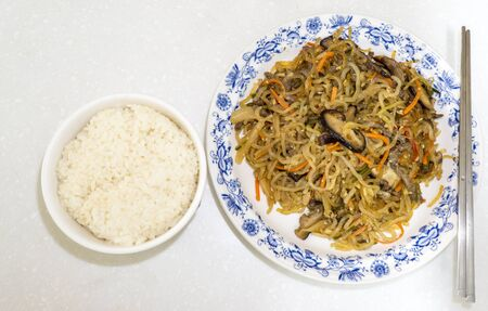 chap: traditional korean dish called japchae which is made from sweet potato noodles stir fried in sesame oil.  Taken with metal chopstick on the plate and a bowl of rice next to it