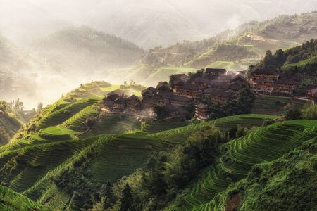 covered fields: beautiful morning view over tian tou zhai village in longji rice terrace in guangxi province of China. Mountains filled with rice fields covered in shroud of morning fog. Stock Photo