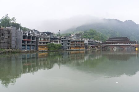 alongside: fenghuang old town morning view with tuojiang river and town alongside it. Morning fog in the distance.