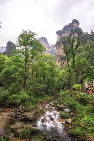 obelisk stone: creekside view with a small bridge. Yangjiajie scenic area in china. Tall obelisk stone with deep valleys.
