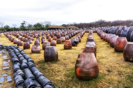 rooftiles: array of traditional korean clay pots in jeju stone park in south korea.
