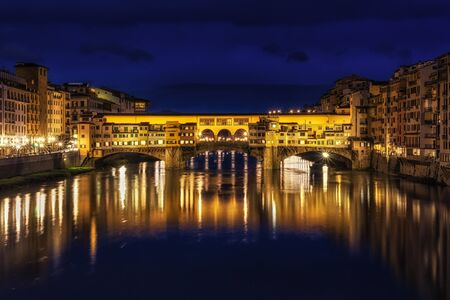 Ponte Vecchio and the buildings close by at night reflecting on the river Arno. Florence, italy Stock Photo