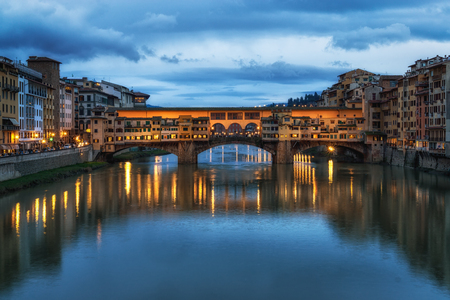 Ponte Vecchio and the buildings close by at night reflecting on the river Arno .
