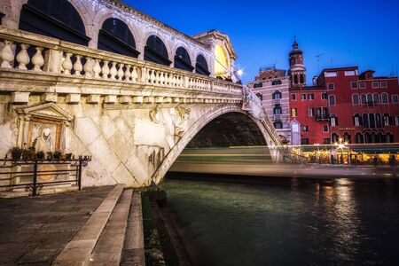 Boats rushing through the rialto bridge in Venice, Italy