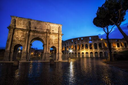 Colosseum and Constantine Arch at Night with the light trails in the nearby road.