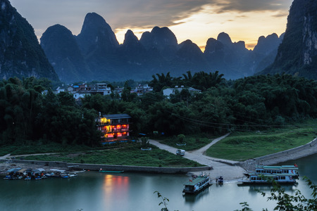 a small red hotel by the li river lit up at night by the lanterns. Taken near laozhai mountain in Xingping, Guangxi province, China.