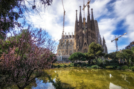 Sagrada familia cathedral view with the small pond and park nearby. Taken in Barcelona, Spain