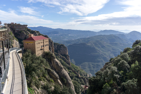Exterior view of Montserrat abbey with the railroad and the view of the mountain range. Taken in Catalonia, Spain