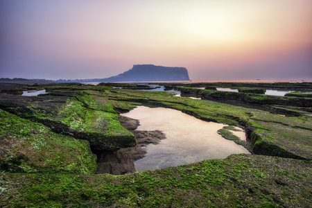 The sunrise view over seongsan ilchulbong on the gwangchigi beach in jeju island, south korea