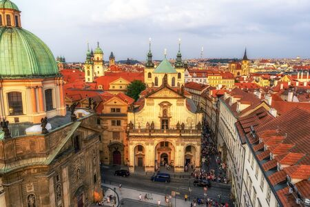 crowds of people gathering in front of saint francis of assisi church and church of saint salvator taken from the old town bridge tower in prague, czech republic. Taken on August 25th 2019