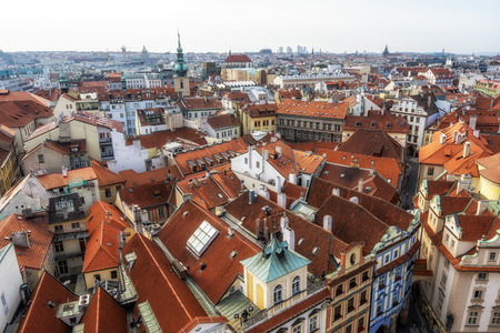 Orange colored roof tops of Prague old town buildings and baroque style houses viewed from top of old town hall tower, Prague, Czech Republic.