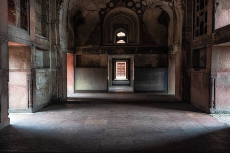 agra fort, a historical fort, dark hallways with light through the multiple doors Taken in India.