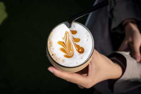 A glass of Ice caramel latte with a simple latte art. Taken from top down Stock fotó