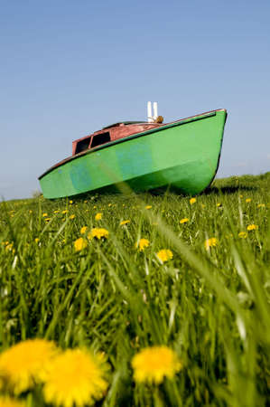 green boat: Green boat sailing over spring meadow Stock Photo