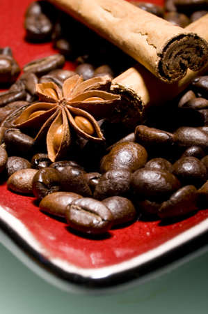 Coffee beans and cinnamon sticks on red plate with anice photo