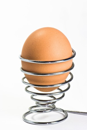 egg on metal eggcup on white background photo