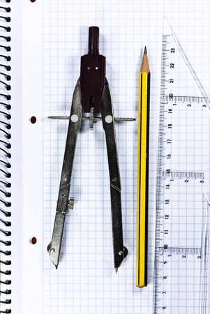 pencil, compass and ruler on notebook texture photo