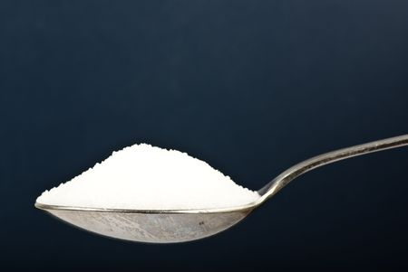 sugar on spoon on dark background photo