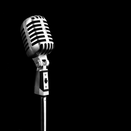 old microphone: metal vintage microphone on black background Stock Photo