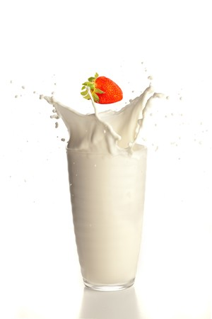 strawberry splashing into milk glass photo