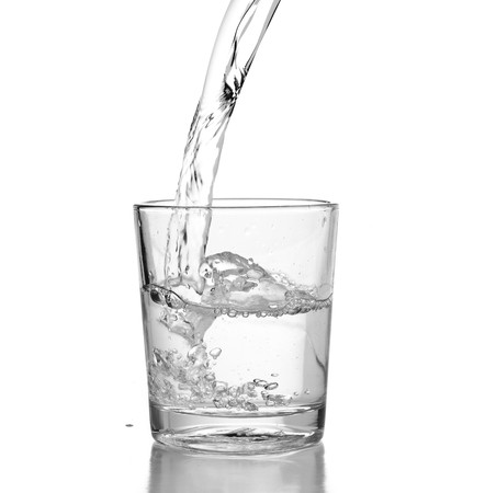 pouring water on glass Stock Photo