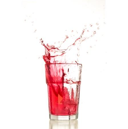 Cocktail splashing on a glass on white background photo