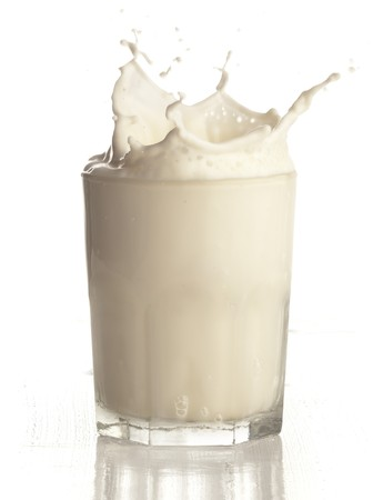 milk splashing into glass on white background photo