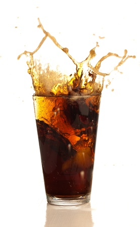 beverage splashing into glass on white background photo