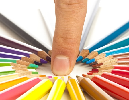 closeup of crayons and one finger on white background photo
