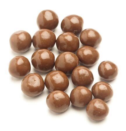 praline: Chocolade granen ballen op een witte achtergrond