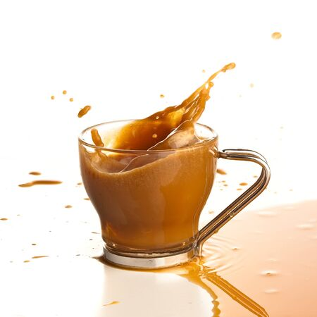 coffee splashing into cup on a white background photo