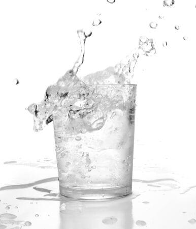 water splashing into glass on white background photo