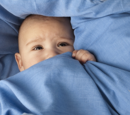 ojos tristes: beb� miedo bajo un portarretrato de manta azul