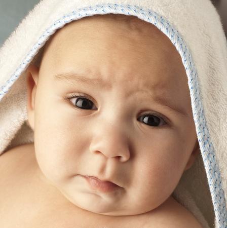 personas tristes: triste beb� en una toalla, portarretrato extrema Foto de archivo
