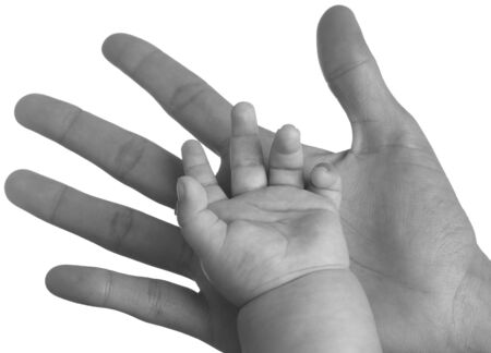 adult hand holding a baby hand closeup, black and white photo